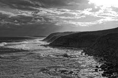 Mar tempestuoso en la costa rocosa blanco y negro imágenes de archivo libres de regalías