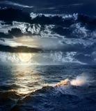 Mar tempestuoso en la noche con el cielo dramático y la luna grande Imágenes de archivo libres de regalías