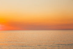 Mar tranquilo u océano y fondo claro amarillo de la puesta del sol o del cielo de la salida del sol Foto de archivo libre de regalías