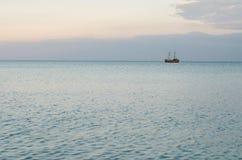 Mar tranquilo y un barco de madera en el horizonte Fotos de archivo
