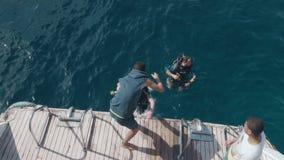 Mar Vermelho 2018 de Egito O mergulhador de mergulhador do movimento lento salta na água da borda do barco com a ajuda de uma ter filme
