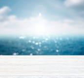 Mar y cielo azules borrosos con el espacio en la tabla de madera fotos de archivo