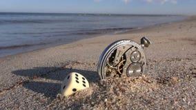 Mar y concepto afortunado del tiempo Dados y reloj viejo en la playa metrajes