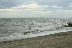 Mar y la costa en un día de invierno tempestuoso, visto de una playa adentro Foto de archivo libre de regalías