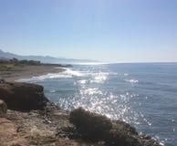 Mar y montañas azules chispeantes vistos de afloramiento rocoso Fotografía de archivo