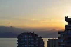 Mar y montañas en puesta del sol con un tejado de la casa multy del piso en primero plano imagen de archivo
