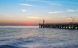 Mar y un embarcadero en la puesta del sol Imagen de archivo libre de regalías