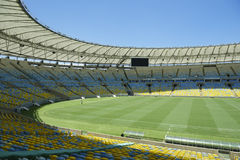 Maracana Football Stadium Seating and Pitch. Empty blue and yellow stadium seating surrounding green pitch at Maracana football stadium Rio de Janeiro Brazil Stock Photos