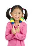 Maracas. A young asian girl playing maracas Royalty Free Stock Image