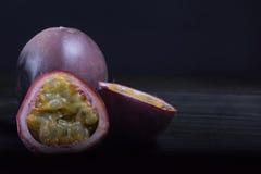 Maracuja et x28 ; passion-fruit& x29 ; dans l'arrangement déprimé de lumière naturelle sur l'obscurité Photo stock