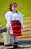 Maramures traditional girl. A young girl dressed in specific handmade clothes with a bucket in her hand in Maramures, Romania Royalty Free Stock Photos