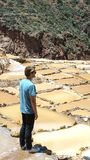 Maras, Cusco, Peru - 01.05.2019. handsome man looking at shallow pools with salt pans in Salinas de Maras Urumbamba valley in Peru. Top tourist attraction in royalty free stock photography