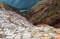MARAS, REGIÃO DE CUSCO, PERU 6 DE JUNHO DE 2013: As minas de sal de milhares de Maras- de lagoas quadrado-dadas forma desiguais p imagens de stock royalty free