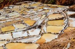MARAS, REGIÃO DE CUSCO, PERU 6 DE JUNHO DE 2013: As minas de sal de milhares de Maras- de lagoas quadrado-dadas forma desiguais p fotografia de stock royalty free