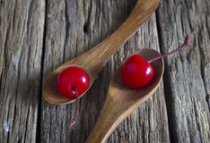 Maraschino cherry vibrant on wooden spoon and old table background Stock Images