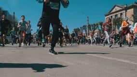 Maratón de la ciudad Muchedumbre de corredores de la gente y de los atletas funcionados con a lo largo del camino en la ciudad metrajes