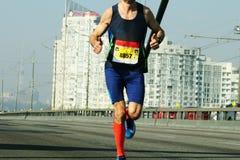 Marathon die in het ochtendlicht lopen Jonge mens die op de weg van de stadsbrug lopen Het lopen op stadsweg De voeten van de atl stock afbeelding