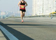 Marathon die in het ochtendlicht lopen Jonge mens die op stadsbrug lopen Het lopen op stadsweg De voeten van de atletenagent Blur royalty-vrije stock foto's