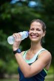 Marathon female athlete running drinking water. In park Stock Photography