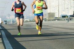 Marathon lopend ras, mensenvoeten op stadsweg Groep jonge agenten een paar meters van de aankomst van moeilijke marathon stock afbeelding