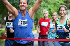 Marathon male athlete crossing the finish line. In park Royalty Free Stock Image