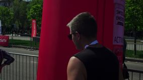 A marathon participant, a young guy, an athlete, in sunglasses, after running, walking along the track, through the city stock footage