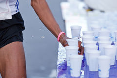Marathon racer catching cup of water Royalty Free Stock Image