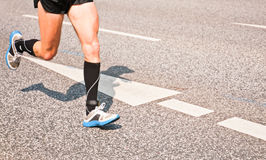 Legs of man running on road. During athletic event stock photography