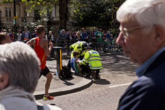 Marathon runner being help by Police Stock Photography