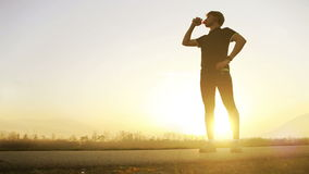 Marathon runner drinks water on the wide angle mountain landscape stock video footage