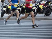 Runner legs running on city road stock photography