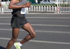 Runner running on city road. Marathon runner running on city road Royalty Free Stock Image