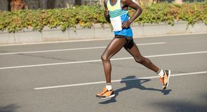 Marathon runner running on city road. African marathon young fitness men runner is running on city road Royalty Free Stock Photo
