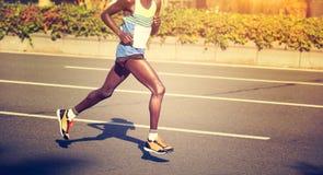 Marathon runner running on city road. African marathon young fitness men runner is running on city road Stock Photo