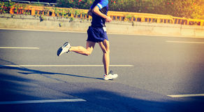 Marathon runner running on city road. Fitness male marathon runner running on city road Royalty Free Stock Images