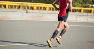 Marathon runner running on city road. Fitness male marathon runner running on city road Royalty Free Stock Image