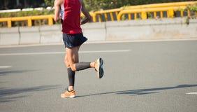 Marathon runner running on city road. Fitness male marathon runner running on city road Royalty Free Stock Photos