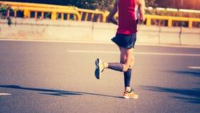 Marathon runner running on city road. Fitness male marathon runner running on city road Stock Image
