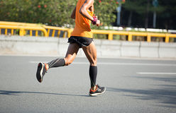 Marathon runner running on city road. Fitness male marathon runner running on city road Stock Photo