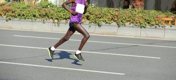 Marathon runner running on city road. Male marathon runner running on city road Royalty Free Stock Photos