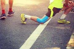 Marathon runner stretching legs. On road Stock Photo