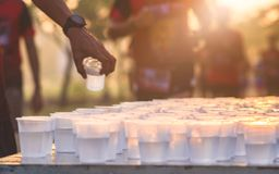 Marathon Runner take a water at a service point in a marathon ra royalty free stock image