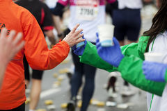 Marathon runner taking cup of water at the refresm Stock Images