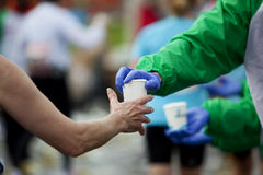 Marathon runner taking cup of water at the refresm Royalty Free Stock Image