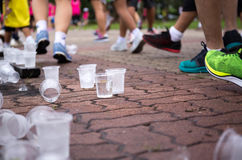 Marathon runners feet and emptry water cups on refreshment point. Marathon runners feet and emptry plastic water cups on refreshment point Royalty Free Stock Photography