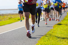 Marathon runners. Group of runners compete in the race on coastal road Royalty Free Stock Images