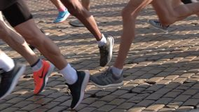 Marathon runners legs only. Slow motion. Sofia, Bulgaria - 13 October 2019: Men and women run during a start of Sofia Marathon running race. Legs and bodies only stock video footage