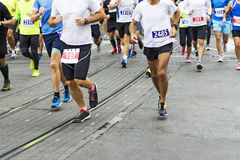 Marathon runners race in city streets Stock Image