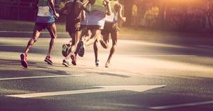 Marathon runners running on city road. Five male marathon runners running on city road Stock Images