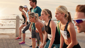Marathon runners taking the position for the start of race. Fitness people about to start a running race on a street by the sea Royalty Free Stock Images